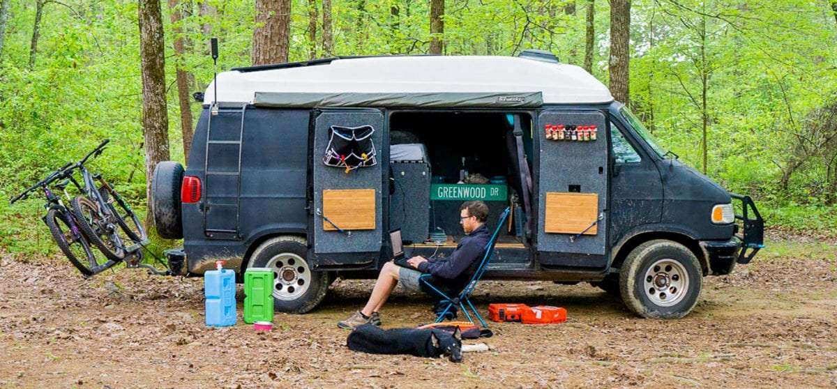 a man sitting in a camping chair, working on a laptop, outside of his van