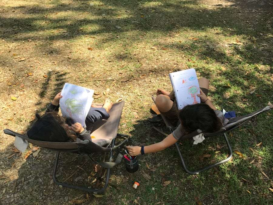 two boys drawing in camping chairs