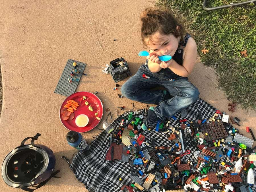 a young boy eating and playing legos
