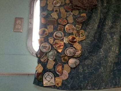 a collection of junior ranger badges and patches hung on a curtain of an airstream