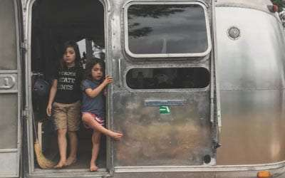 two boys stand in the doorway of a vintage airstream