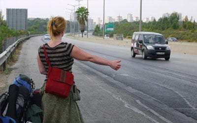 a woman hitchhikes through Europe