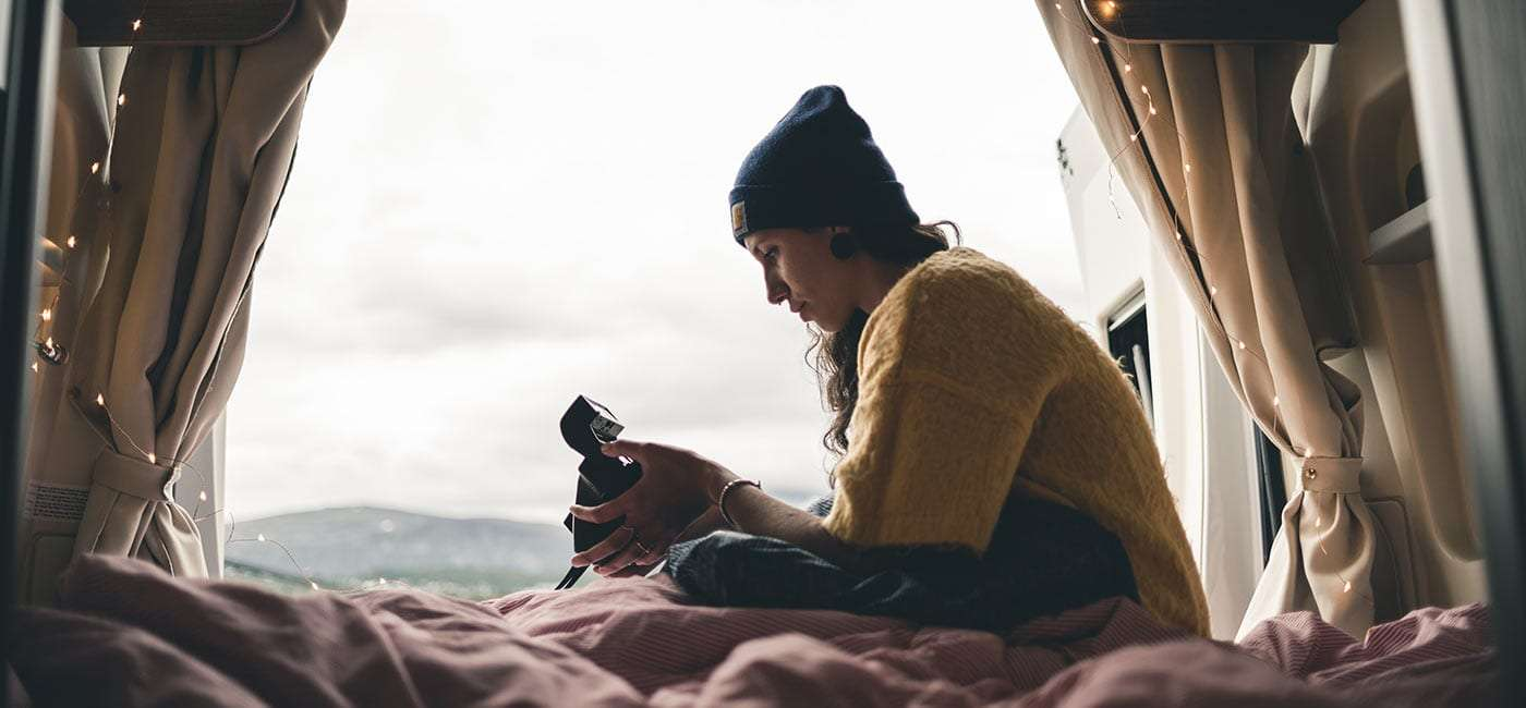 a young woman fiddling with a camera in the back of her van
