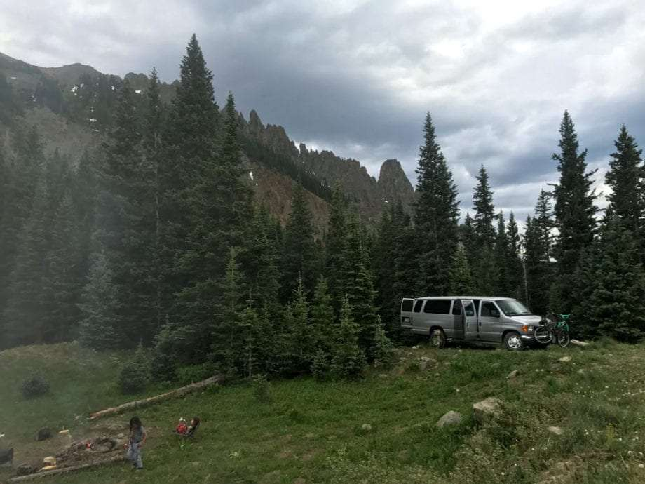 a van camped in a meadow with mountains in the background