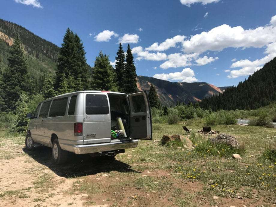 a van parked, camping, along a river and amongst mountains outside of Silverton