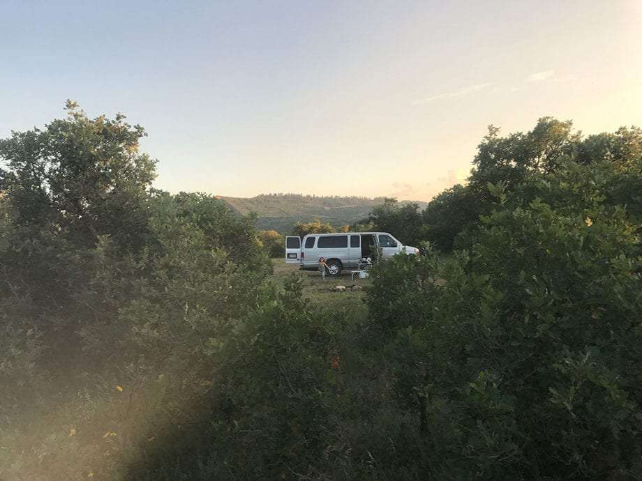 a van camping amongst oak trees
