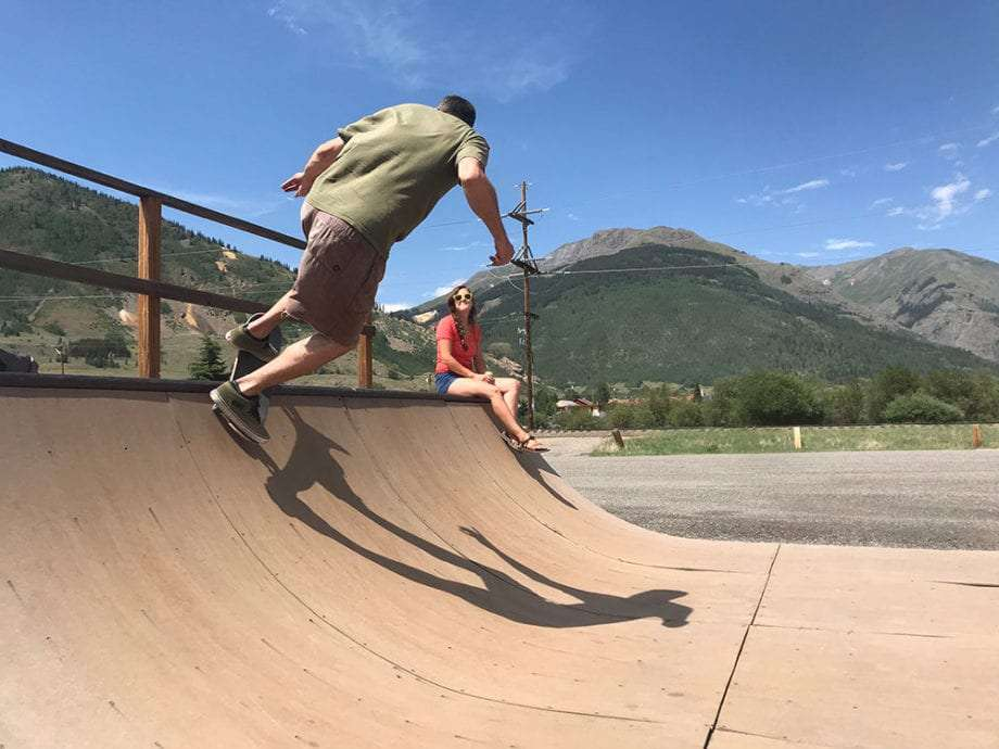 a man skates the coping of a wooden ramp