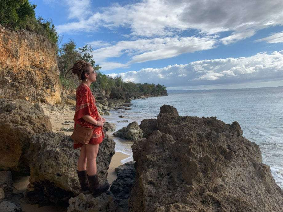 a woman in a red dress looks from a cliff over the Caribbean near Aguadilla, Puerto Rico