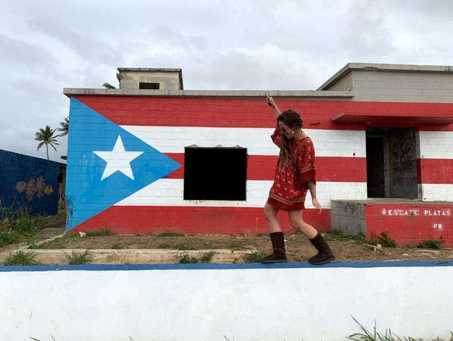 a woman walking in front of a puerto rican flag painted building