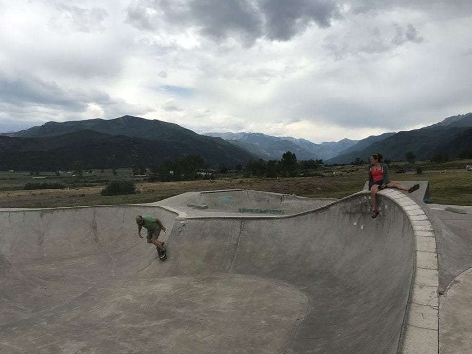 a man rides the bowl at Ridgway's skatepark while his wife watches him from the coping