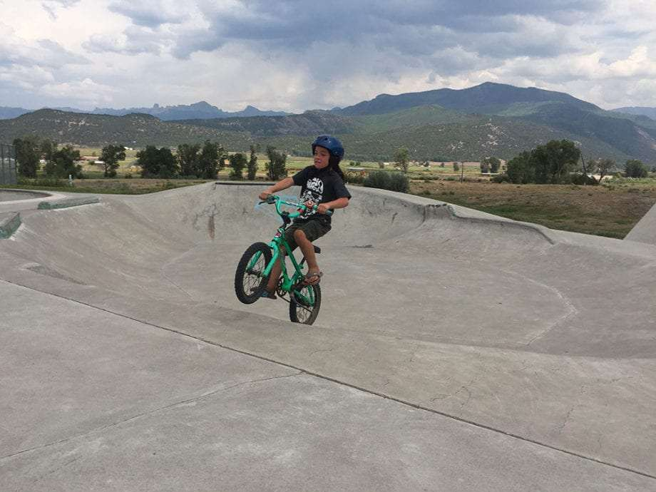 a young boy rides a BMX bike at a skatepark