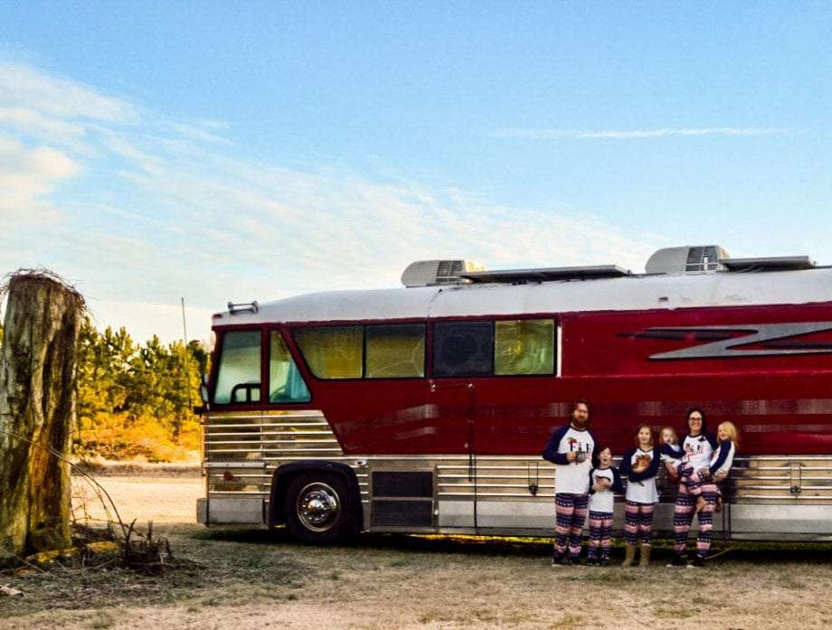 a family of six stands in front of a motorcoach they've converted to be their home on the road