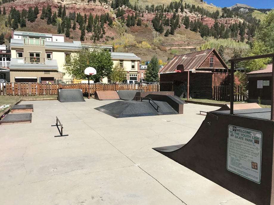 a wooden skatepark with Telluride and its mountains looming in the background