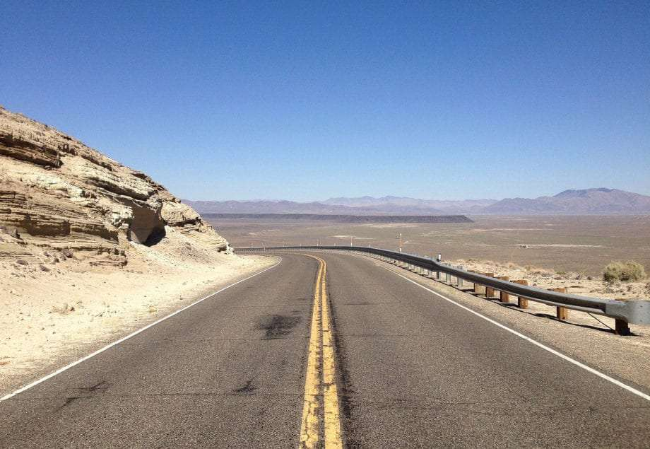 the open road carves through desolate desert with mountains in the distance