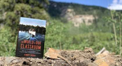 a book on raising your children in the outdoors set against a mountain backdrop