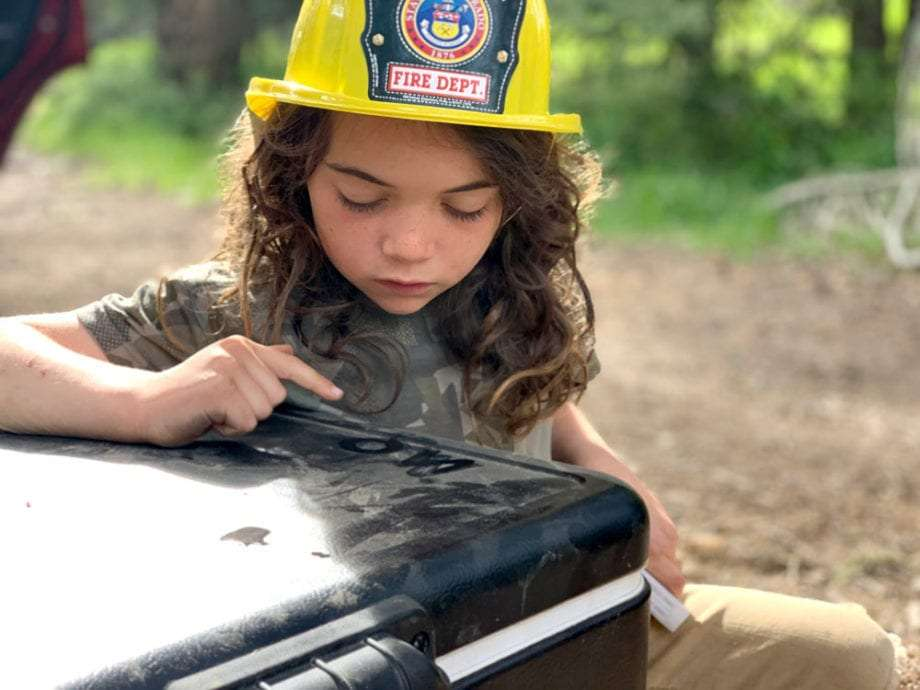 a young boy in a fireman hat draws pictures in the dust of a Coleman cooler