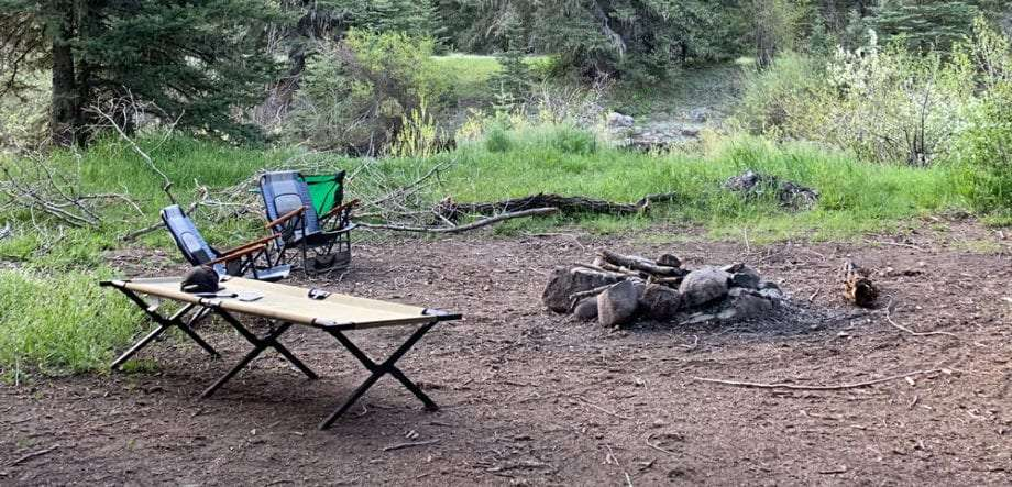 a camping cot positioned near a fire, along with some camping chairs