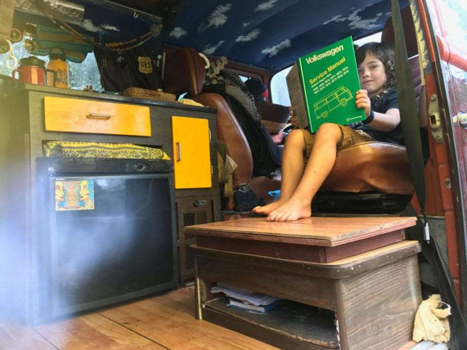 a young man reads a volkswagen manual upside down near a fridge in a VW Bus
