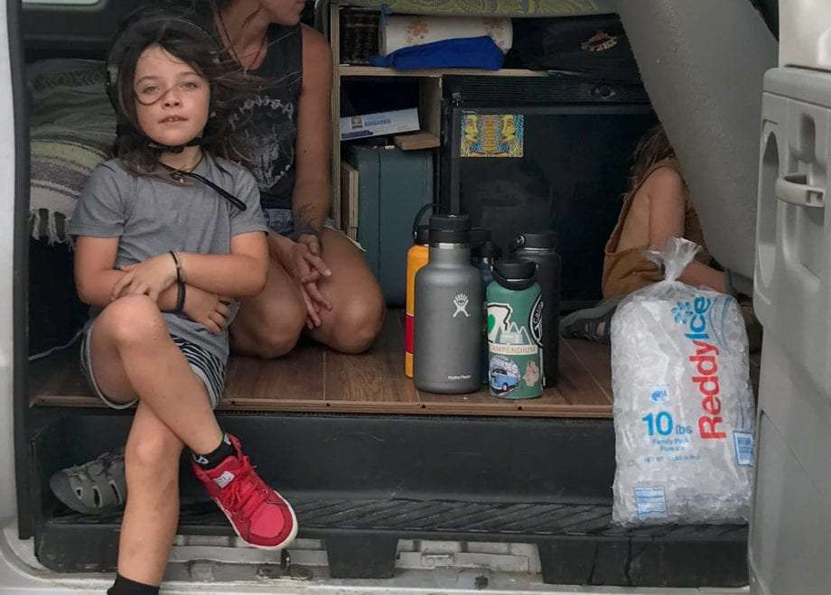 a family in their van with some hydroflasks and a bag of ice