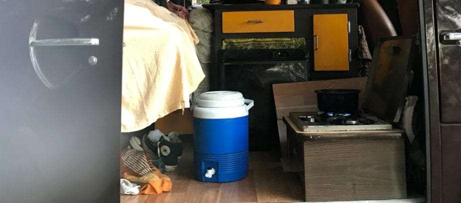 a blue cooler sits on the floor of a campervan