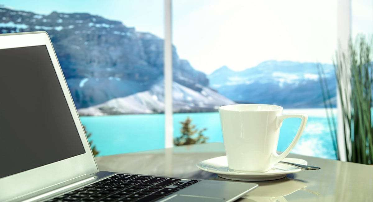 a laptop and cup of coffee rest on a table overlooking a lake and mountains