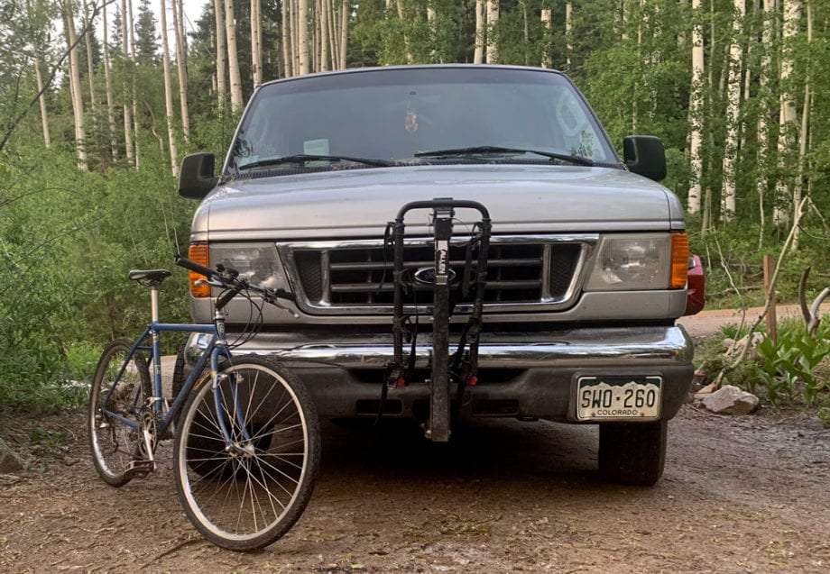a bicycle leaned against a van with a bike rank mounted to the front