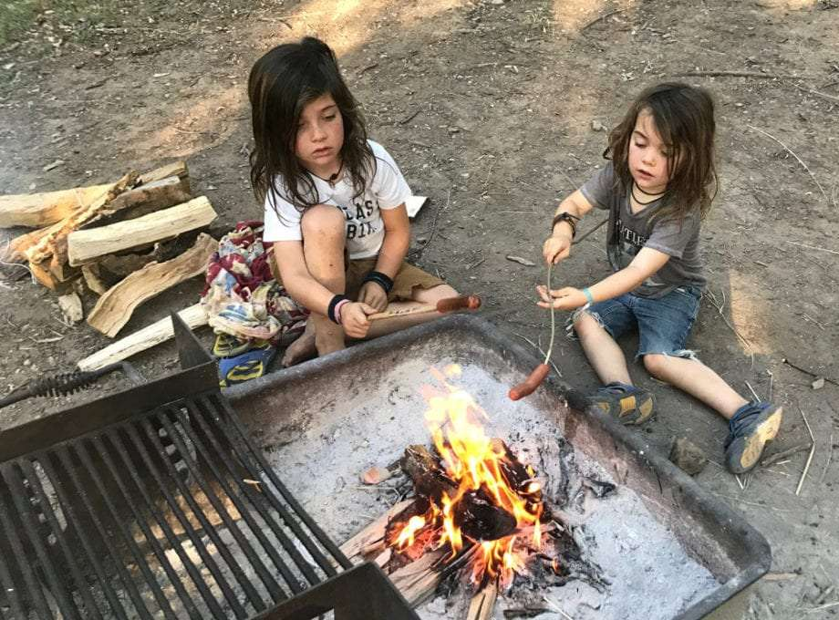 two kids roasting hot dogs on a fire