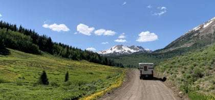 a truck camper roaming a dirt road into the Rocky mountains