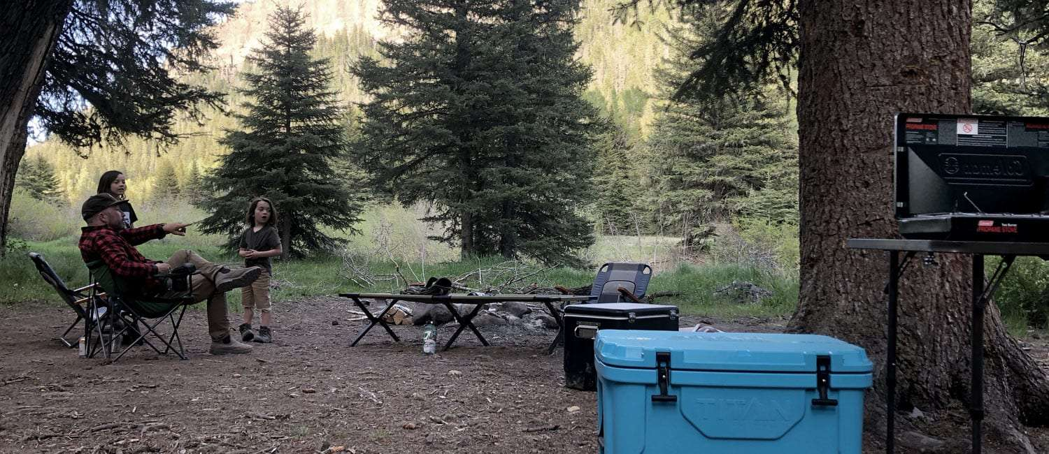 a family camping by a river with loads of camping stuff
