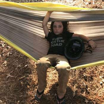 a boy sits in a hammock