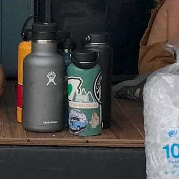 several metal water bottles with stickers on them