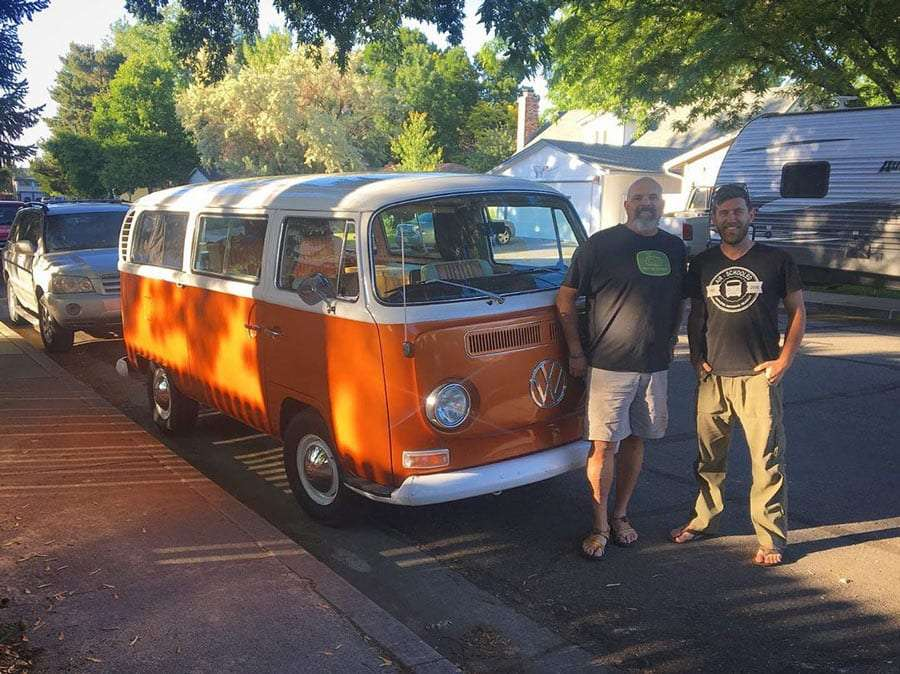 two men stand by a vintage VW Bus