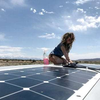 a young boy cleans a solar panel