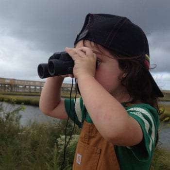 a young boy using binoculars