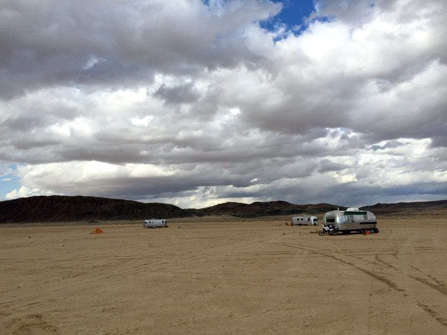 three airstreams parked in a desert surrounded by mountains