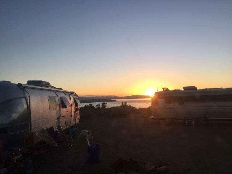 two airstreams parked near mono lake in eastern california, the sun rising beyond them.