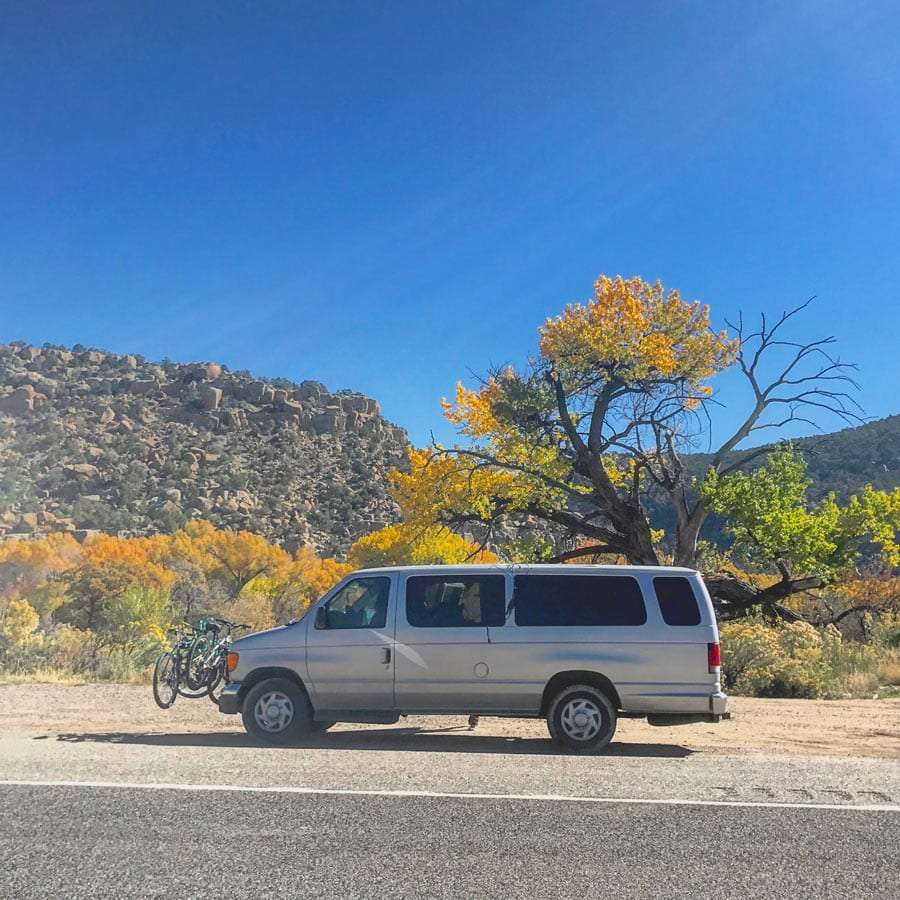 a Ford E-350 parked near a yellow cottonwood tree