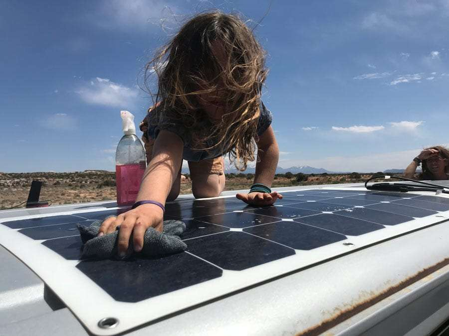 a boy washing solar panels on a van roof