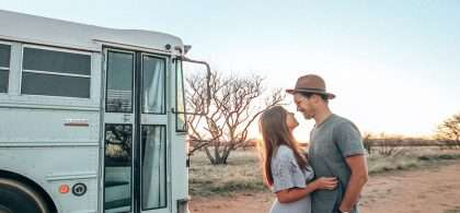 Chase and Mariajose stand outside of their blue converted school bus, looking quite content