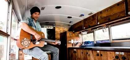 Prem Yogi plays guitar in his converted school bus