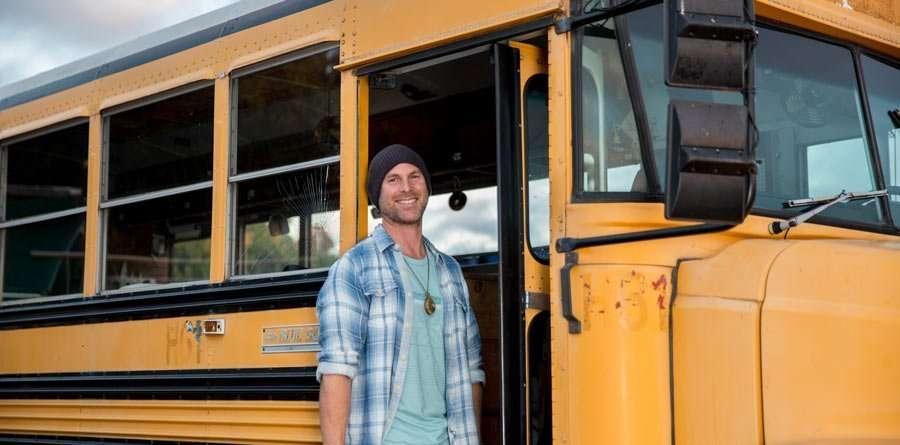 Prem standing in the doorway of his bus.