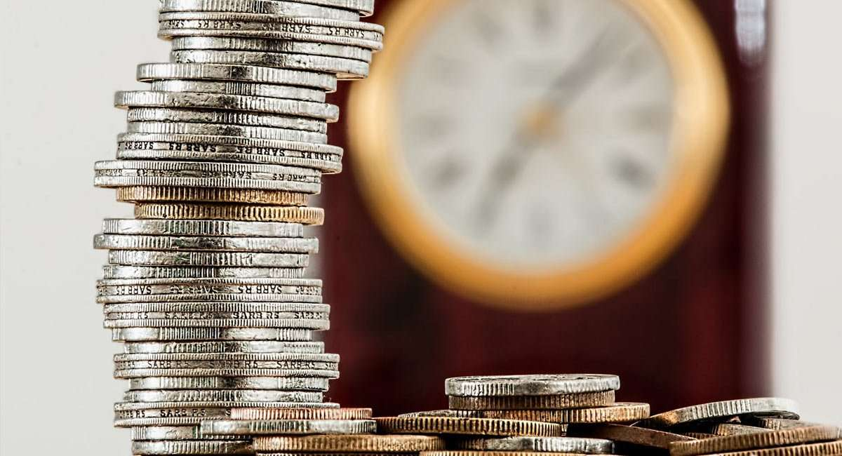 coins stacked, a clock in the background