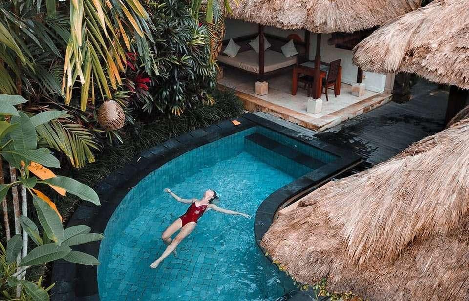 a woman swims in a small pool near tiki huts