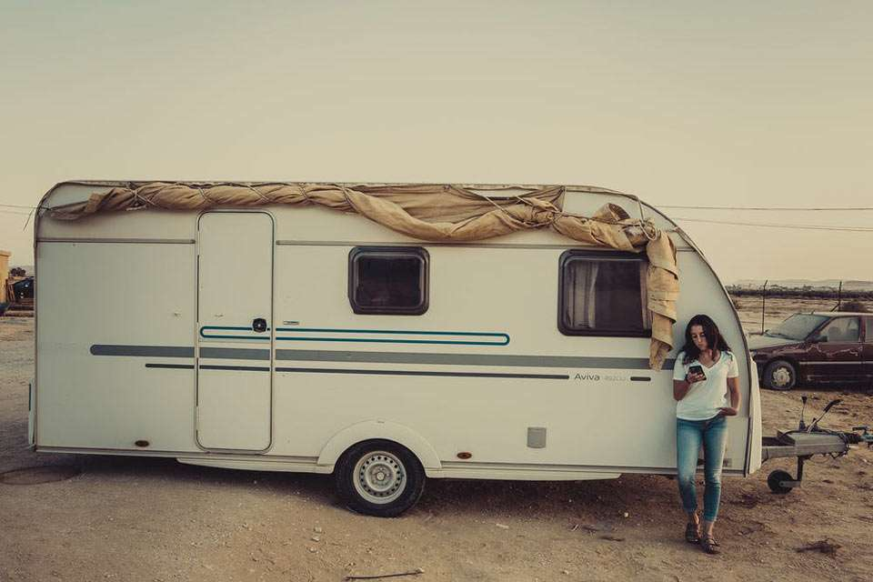 a woman standing in front of a travel trailer