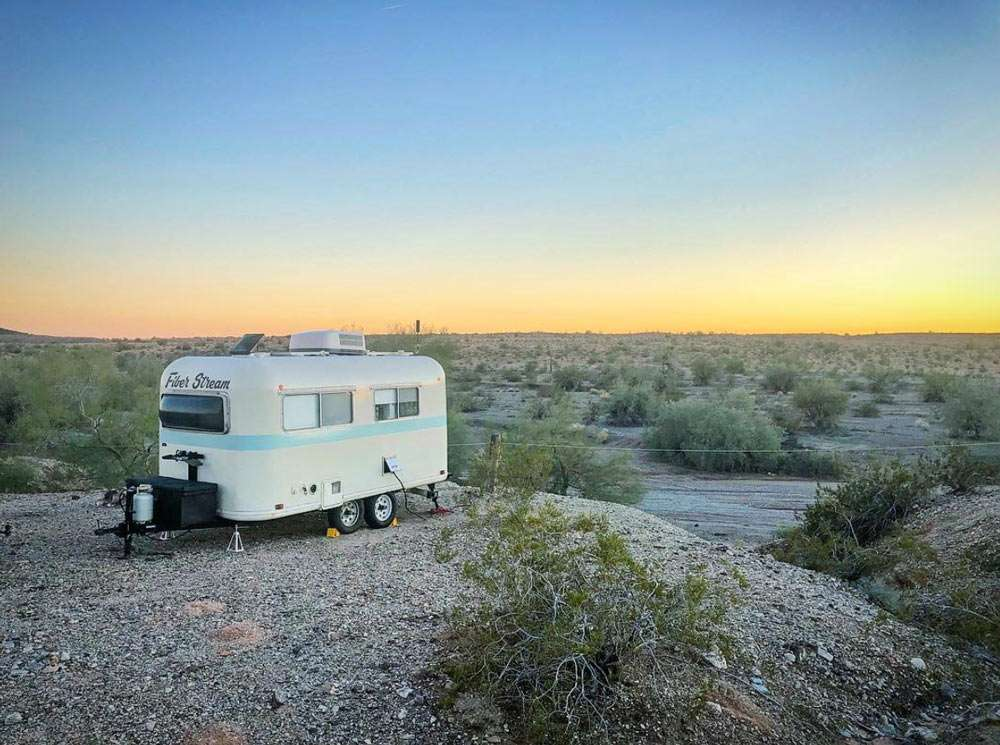 a small travel trailer parked in the desert at sunset