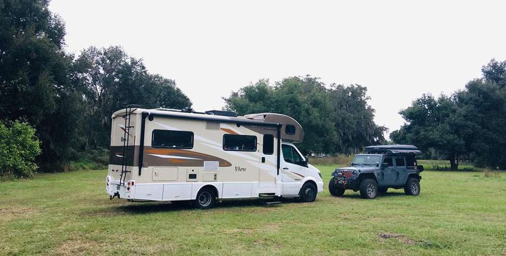 an RV and a Jeep parked in a grassy meadow