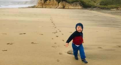 a toddler runs along a beach