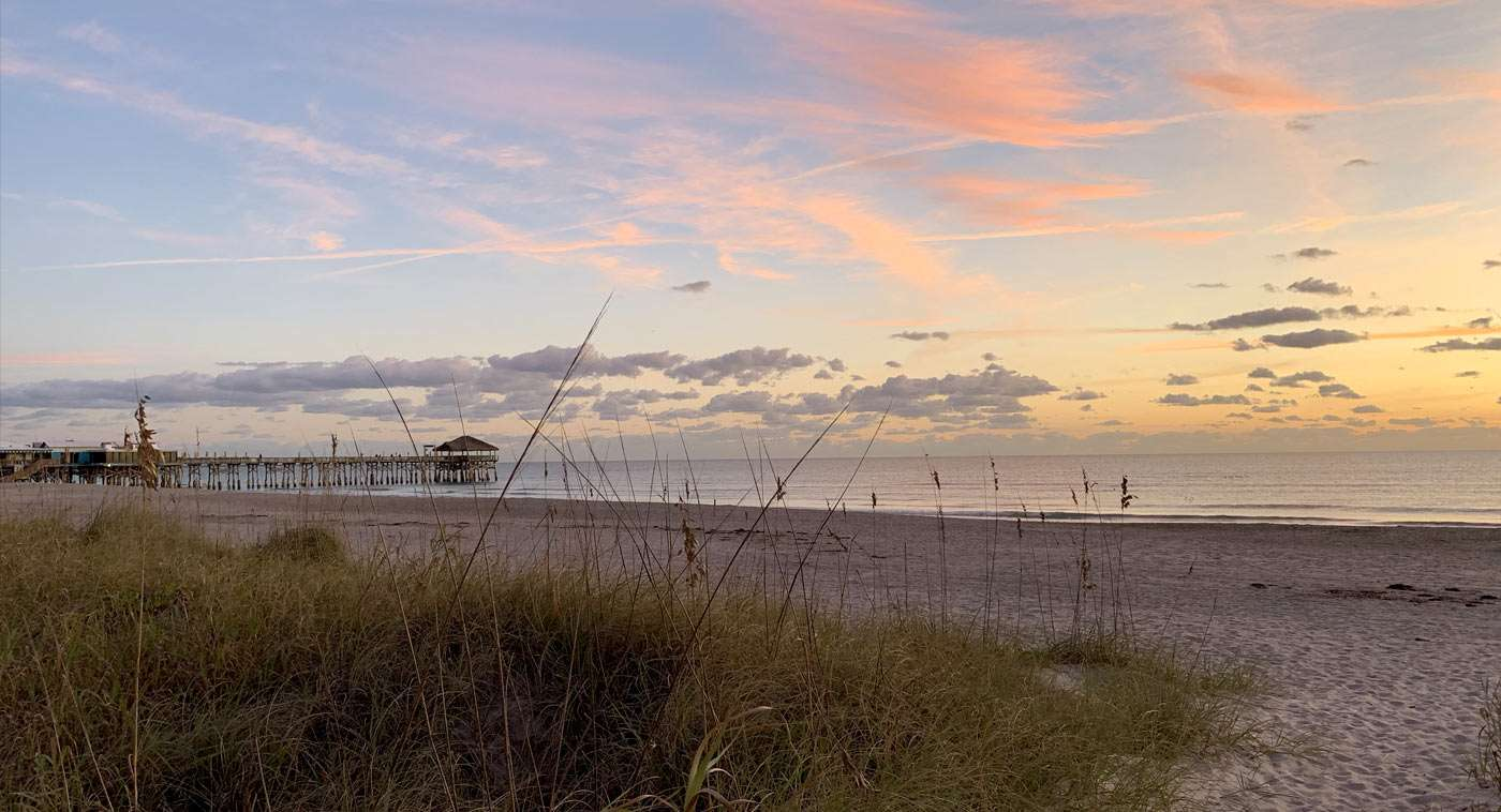 sunrise bouncing off of the clouds near the cocoa beach pier