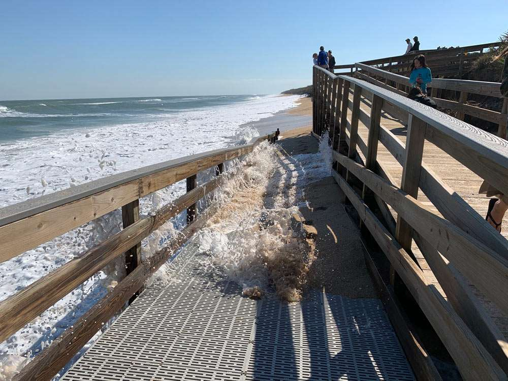 ocean water rushes over a boardwalk