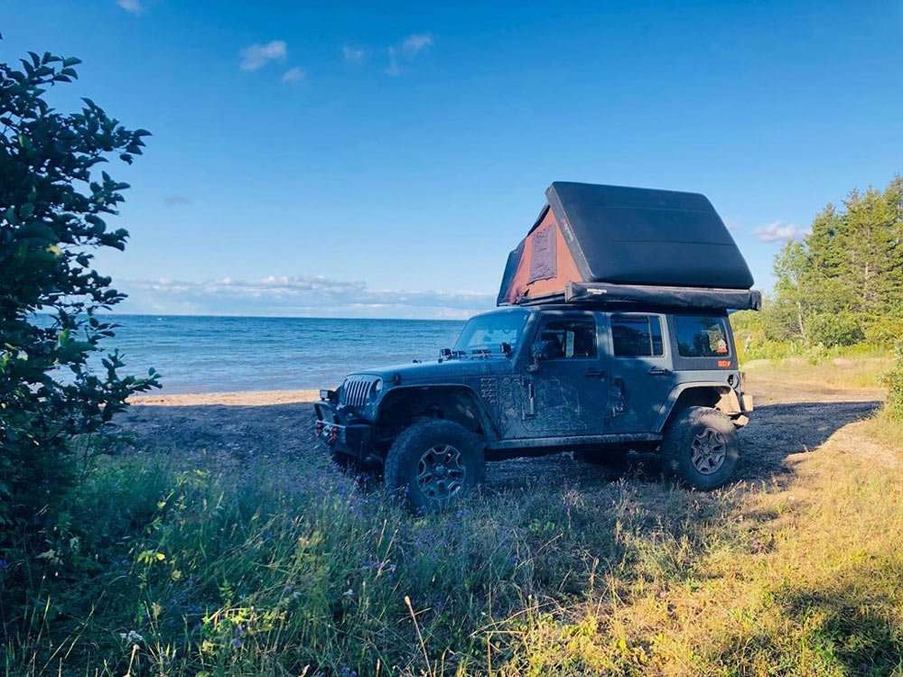 a Jeep with a rooftop tent parked near the coast